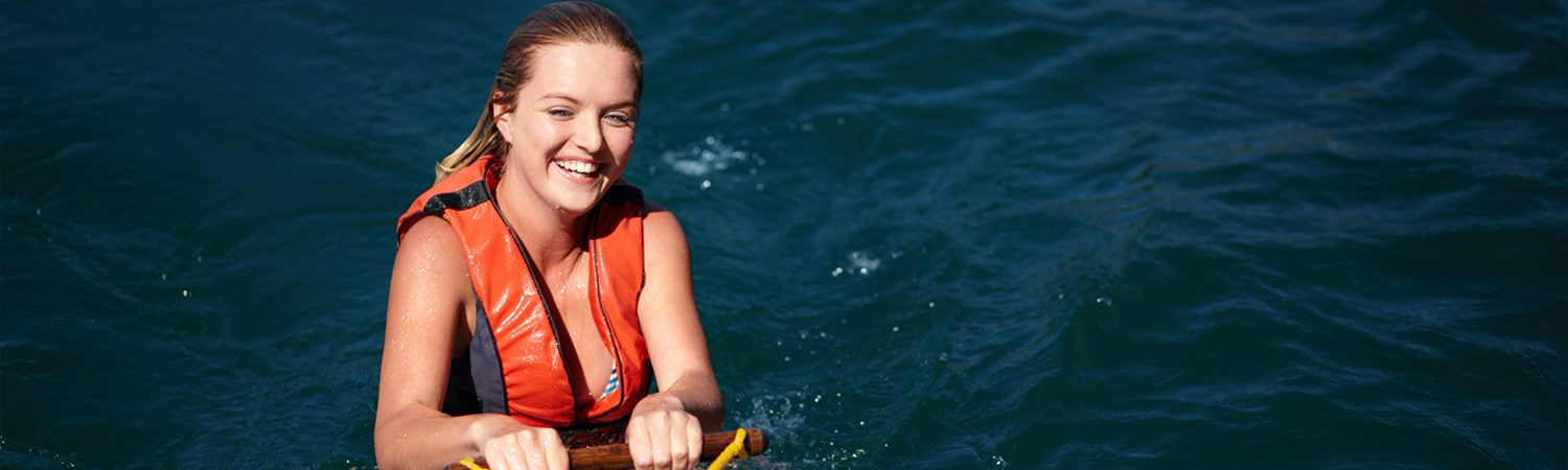 Girl in water smiling holding a water ski handle